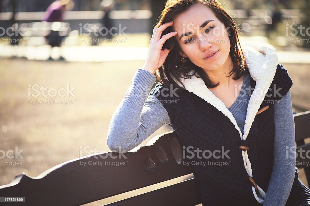 Portrait of young girl sitting on a bench royalty-free stock photo