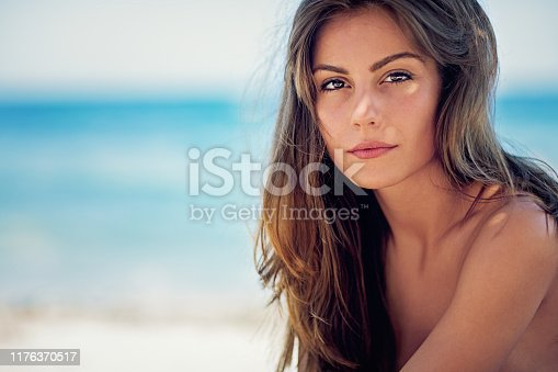 Portrait of young girl standing on the beach and enjoying the ocean