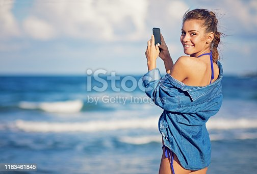 Portrait of young girl taking pictures on the beach