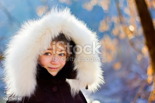 Portrait of young girl wearing fur lined coat hood