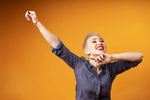 Portrait of young girl with blond short hairstyle looking at camera and laugh isolated on orange background with copy space stock photo