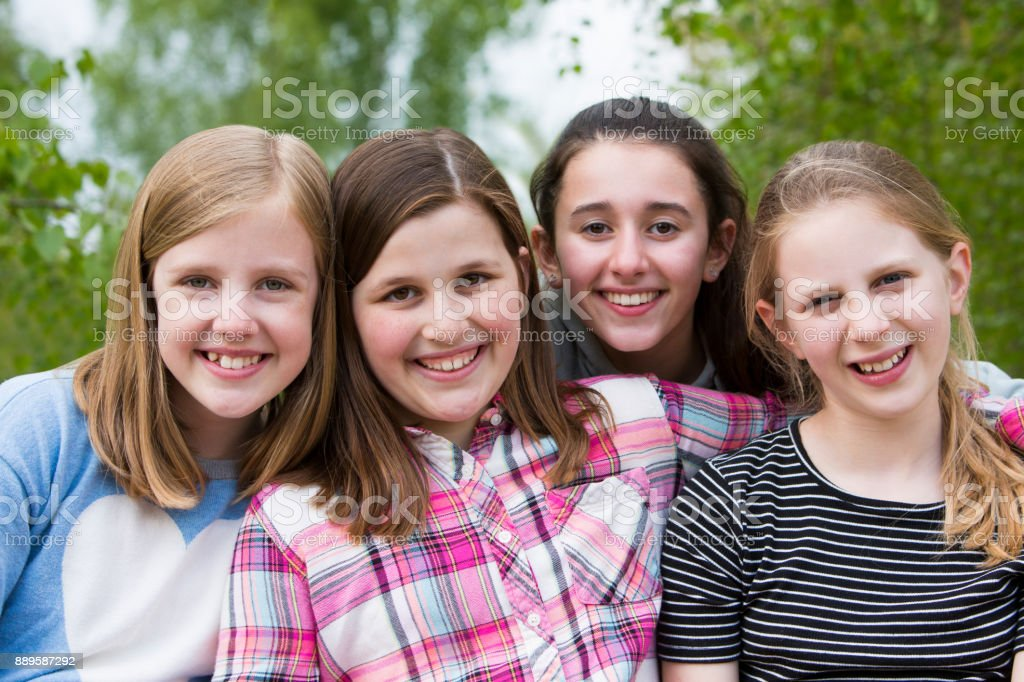 Portrait Of Young Girls Having Fun In Park Together stock photo
