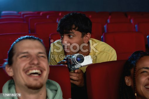 Portrait of young guy using his video camera for recording a pirated movie at the cinema. Selective focus. Horizontal shot