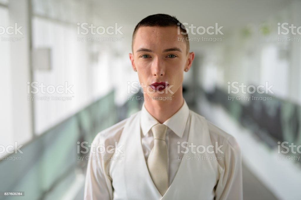 Portrait of young handsome androgynous businessman relaxing on the footbridge at Bangkok Thailand stock photo