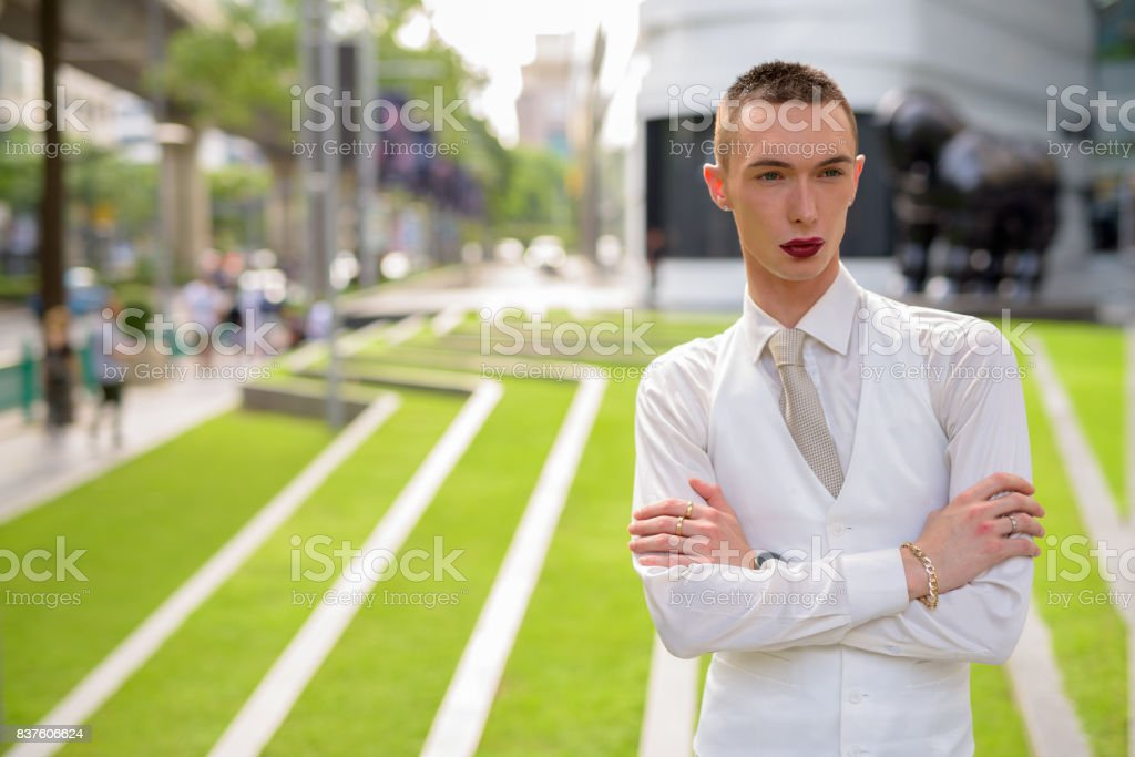 Portrait of young handsome androgynous businessman relaxing outside the building in Bangkok Thailand stock photo