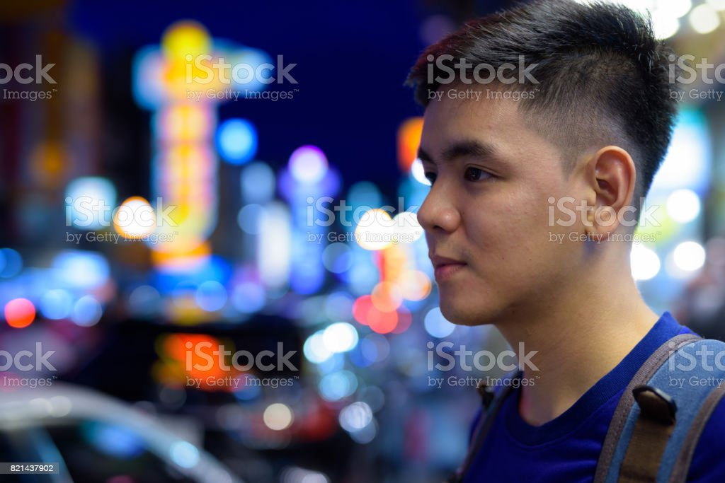 Portrait of young handsome Asian tourist man exploring at Chinatown in Bangkok Thailand stock photo