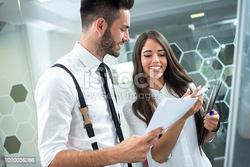 istock Portrait of young handsome boss analyzing paper documents with attractive smiling secretary women in office 1020036266