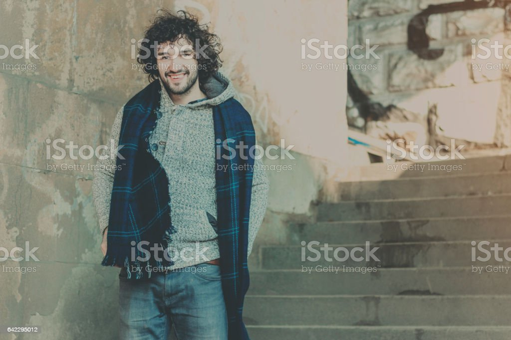 Portrait of young handsome curly hair man posing outdoor stock photo