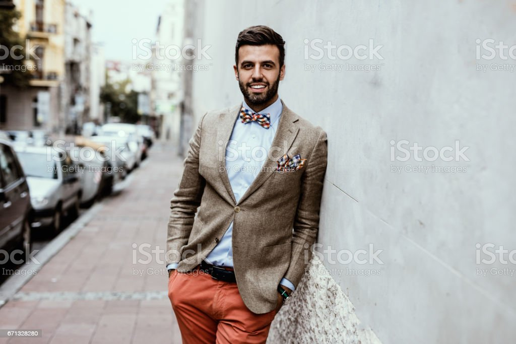 Portrait of young handsome fashion blogger leaned on the wall. stock photo
