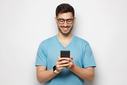Portrait of young handsome guy wearing blue-shirt and glasses looking at phone screen with smile, isolated on gray background