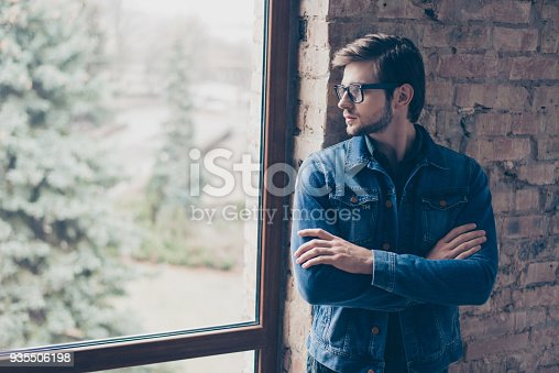 611630440 istock photo Portrait of young handsome guy with glasses and a jeans jacket is standing with  folded his hands and looking thoughtfully out the window 935506198