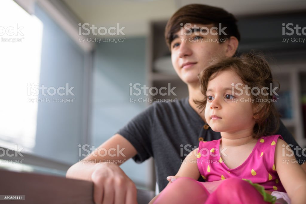 Portrait of young handsome Iranian teenage boy with little sister relaxing at home stock photo