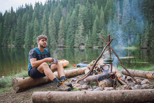 Young attractive male sitting next to campfire, drinking herbal tea and looking away.