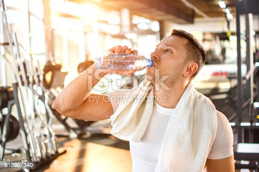 istock Portrait of young handsome man drinking water at gym. 813907340