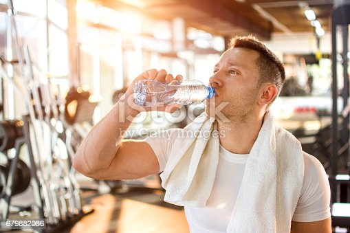 istock Portrait of young handsome man drinking water in a gym. 679882086