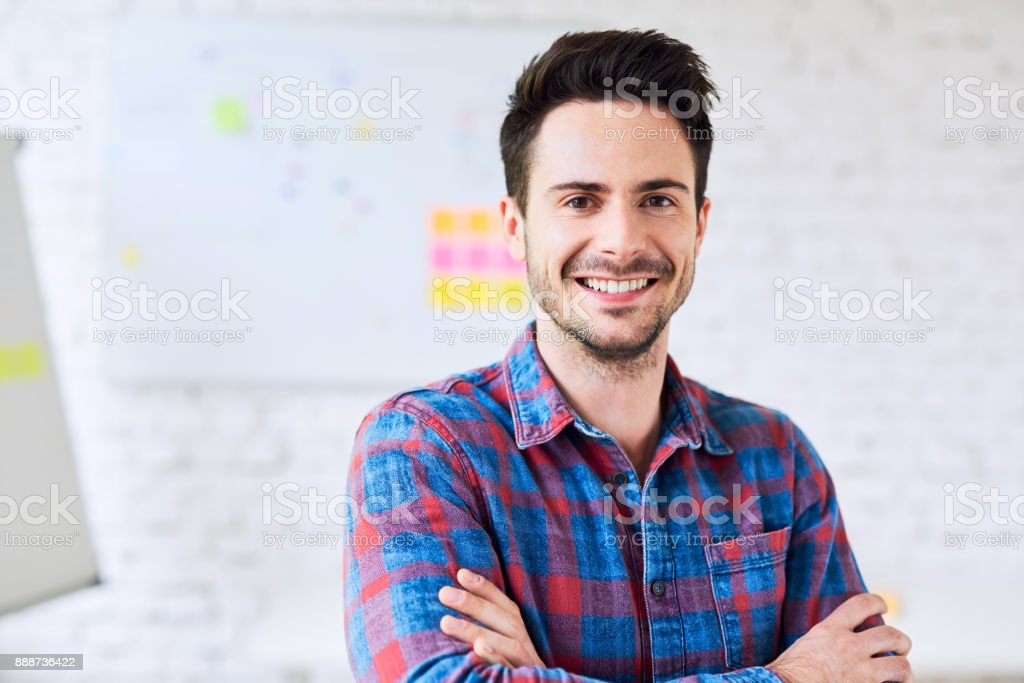 Portrait of young handsome man looking at camera while standing in alternative modern office stock photo