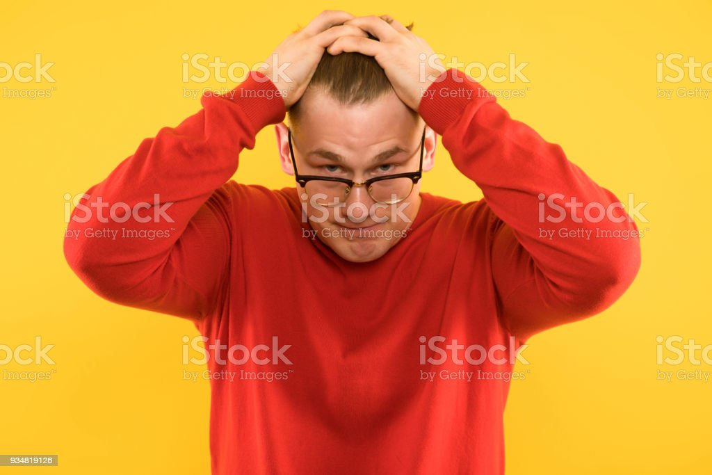 Portrait of young handsome puzzled tired astonished guy under stress on yellow background stock photo
