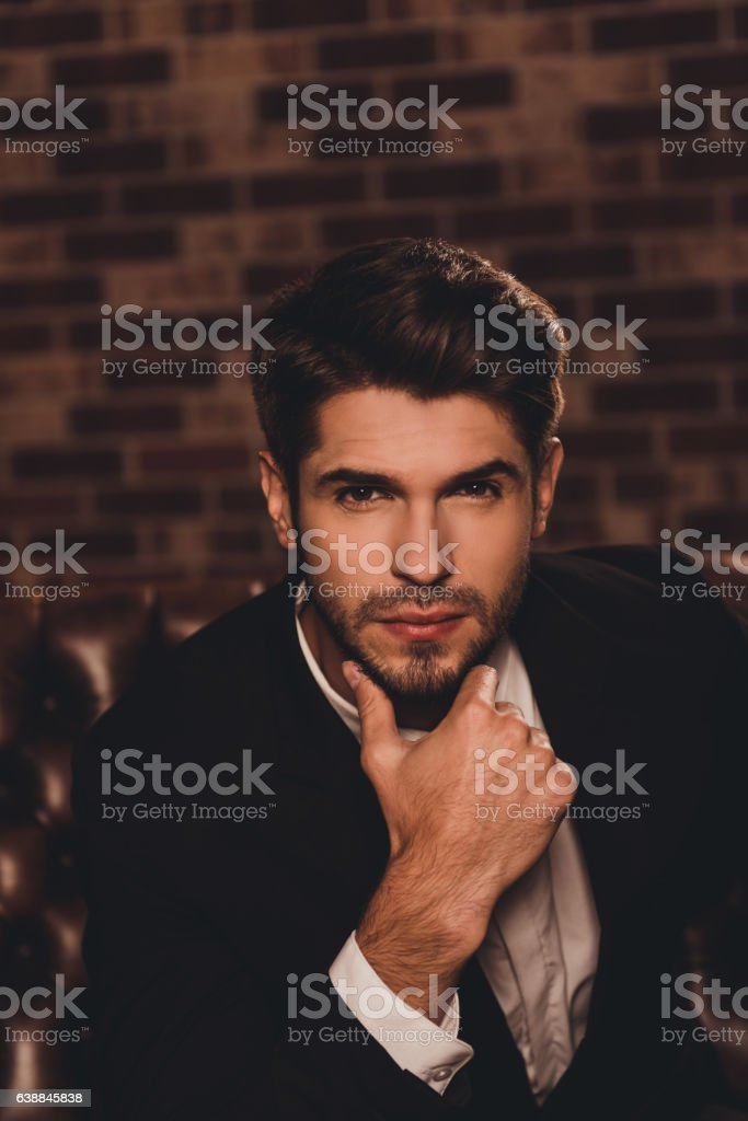 Portrait of young handsome sexy minded man touching chin stock photo