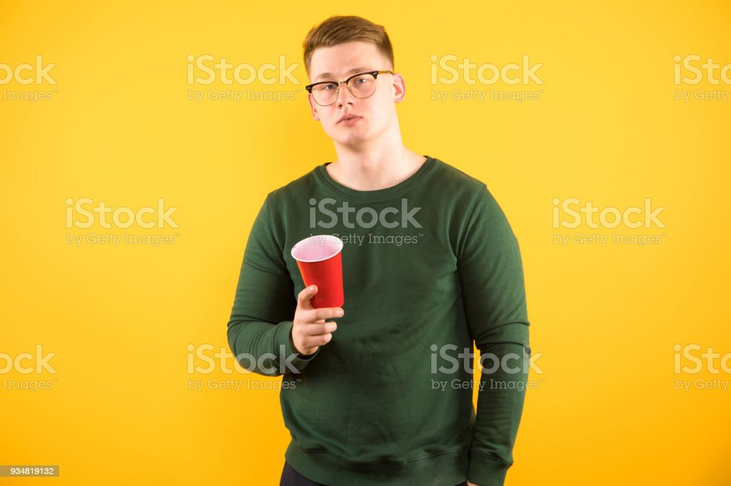 Portrait of young handsome smiling guy holding red plastic cup in his hand on yellow background stock photo