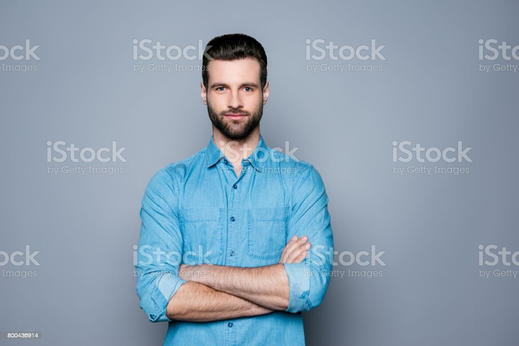 A portrait of young handsome smiling man in jeans shirt standing with crossed hands royalty-free stock photo