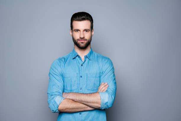 ein porträt der schönen lächelnden jungen mann in jeans hemd stand mit gekreuzten händen - mann bart freisteller stock-fotos und bilder