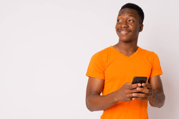 Portrait of young happy African man thinking while using phone stock photo