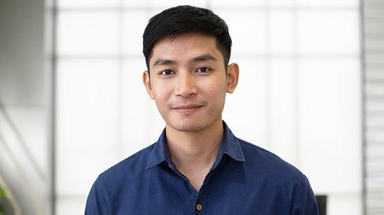 825082848 istock photo Portrait of young happy Asian business man wearing dark blue shirt in casual style on office background, businessman looking at camera, handsome look friendly, smart and confident, successful people 1207166154