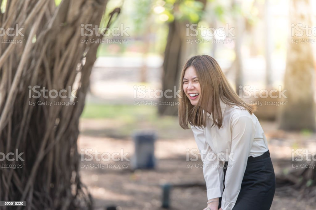 Portrait of Young Happy business woman laughing and smiling. Beautiful Asian girl on blur bokeh Forest sunset background stock photo