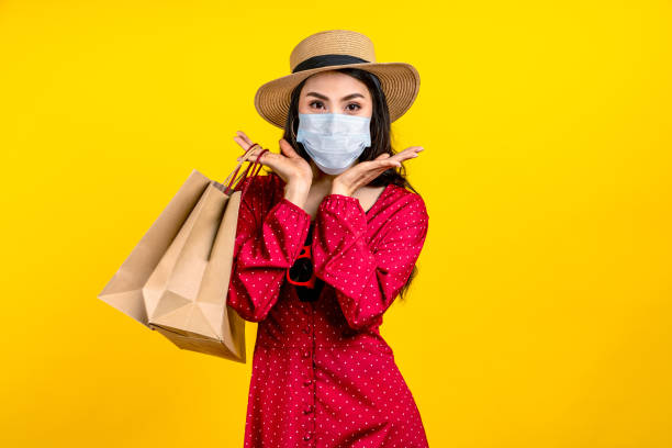 Portrait of young happy carefree asian woman wear hat and facemask carrying shop bag smile on isolated color background in concept back to shopping, new normal summer fashion lifestyle after covid19. stock photo