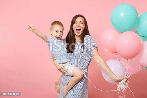 istock Portrait of young happy family, mother keep in arms, have fun, hug child kid son baby boy, celebrating birthday holiday party on pink background with colorful air balloons. Sincere emotions concept. 1015400352