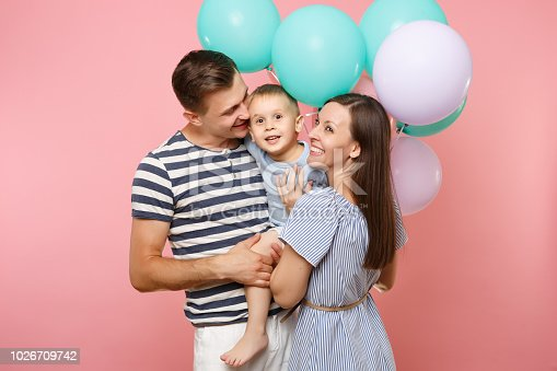 istock Portrait of young happy family, parents keep in arms, kissing hugging child kid son baby boy, celebrating birthday holiday party on pink background with colorful air balloons. Sincere emotions concept 1026709742