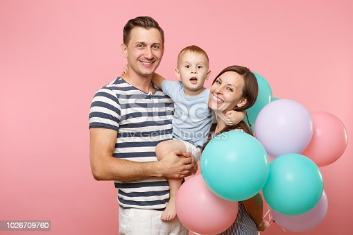 istock Portrait of young happy family, parents keep in arms, kissing hugging child kid son baby boy, celebrating birthday holiday party on pink background with colorful air balloons. Sincere emotions concept 1026709760