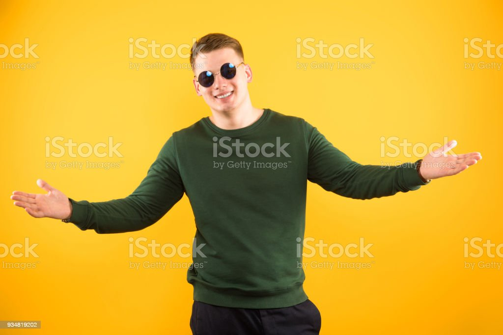 Portrait of young happy handsome smiling guy with sunglasses showing gesture with open arms on yellow background stock photo