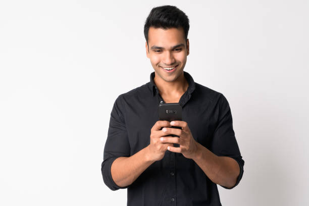 Portrait of young happy Indian businessman using phone stock photo