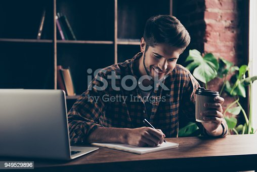 istock Portrait of young happy manager making notes and drinking coffee 949529896