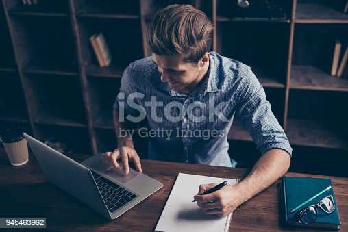 istock Portrait of young happy manager making notes and working with laptop 945463962