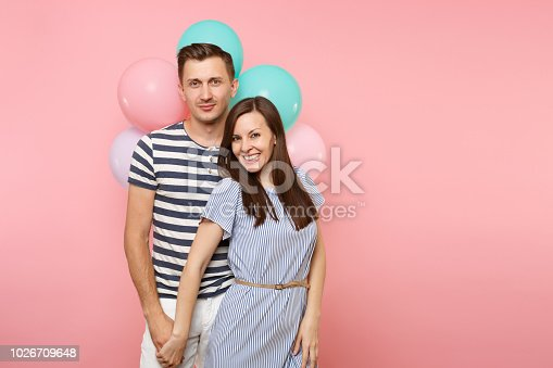 istock Portrait of young happy smiling couple in love. Woman and man in blue clothes celebrating birthday holiday party on pastel pink background with colorful air balloons. People sincere emotions concept. 1026709648