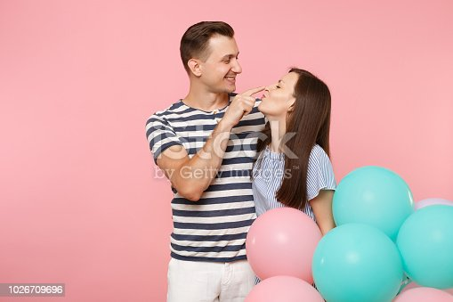istock Portrait of young happy smiling couple in love. Woman and man in blue clothes celebrating birthday holiday party on pastel pink background with colorful air balloons. People sincere emotions concept. 1026709696