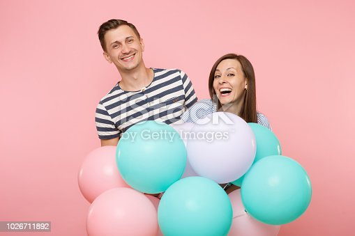 istock Portrait of young happy smiling couple in love. Woman and man in blue clothes celebrating birthday holiday party on pastel pink background with colorful air balloons. People sincere emotions concept. 1026711892