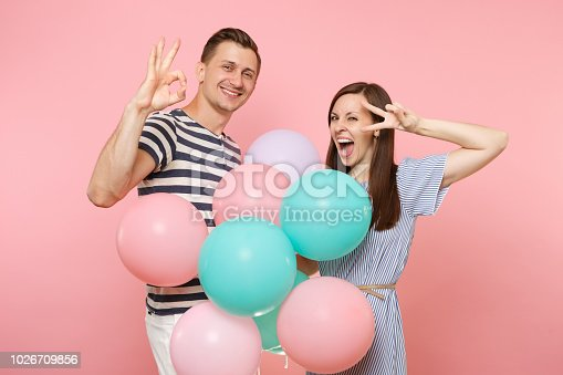 istock Portrait of young happy smiling couple in love. Woman, man in blue clothes celebrating birthday holiday party on pastel pink background with colorful air balloons. People sincere emotions concept ok. 1026709856