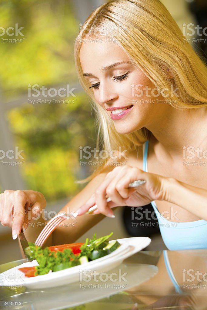 Portrait of young happy smiling woman eating salad royalty-free stock photo