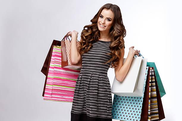 porträt des jungen glücklich lächelnde frau mit einkaufstüten  - kleider günstig kaufen stock-fotos und bilder