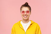 istock Portrait of young happy teenage girl wearing yellow hoodie and colored glasses, feeling relaxed and smiling happily, isolated on pink background 1247694581