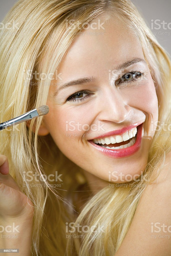 Portrait of young happy woman applying eye-shadow 免版稅 stock photo