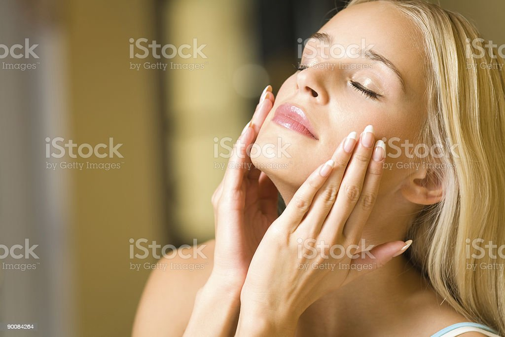 Portrait of young happy woman applying facial cream stock photo