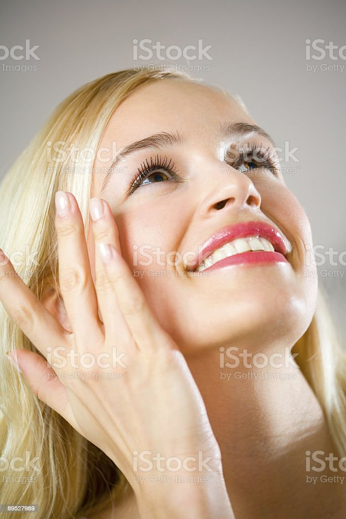 Portrait of young happy woman applying make-up royalty-free stock photo