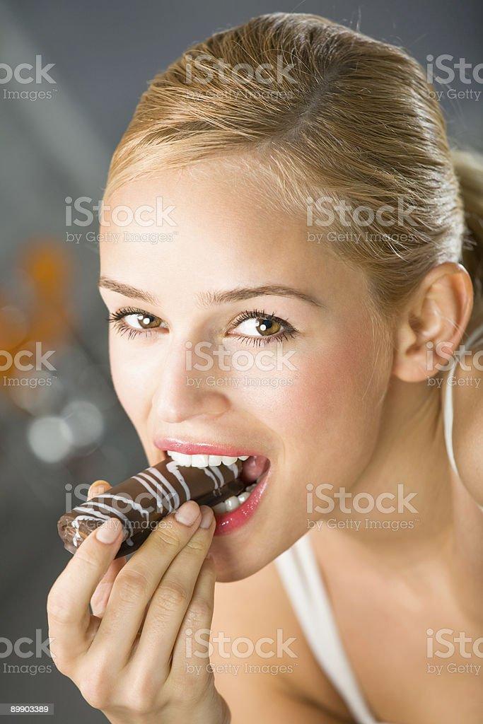 Porträt des jungen glücklich Frau Essen Süßigkeiten im kitchen Lizenzfreies stock-foto