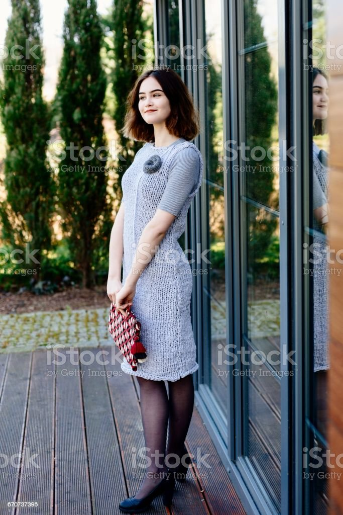 Portrait of young happy woman in grey knitted dress stock photo
