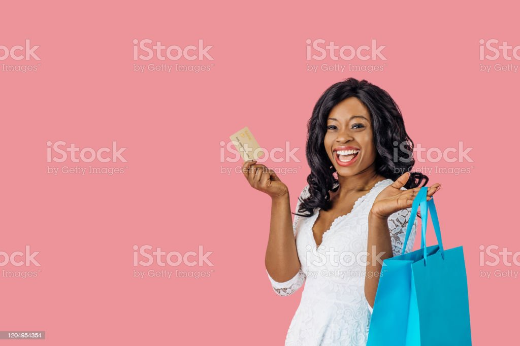 Portrait of young happy woman with shopping bag and credit card looking at camera excited Portrait of young happy woman with shopping bag and credit card looking at camera excited 20-29 Years Stock Photo