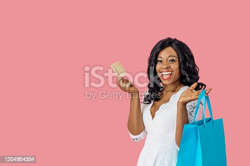 Portrait of young happy woman with shopping bag and credit card looking at camera excited